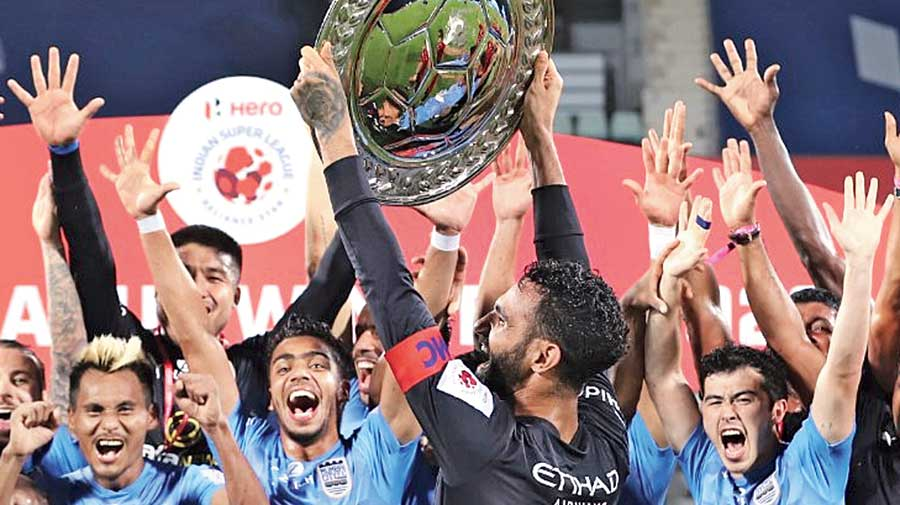 Mumbai City captain Amrinder Singh holds the Winners Shield as teammates celebrate after defeating ATK Mohun Bagan on Sunday.