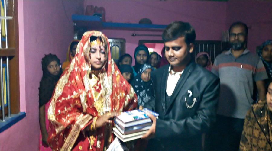 Mizanur Rahman hands over books to Moyna Khatun at Suti in Murshidabad district on Monday.