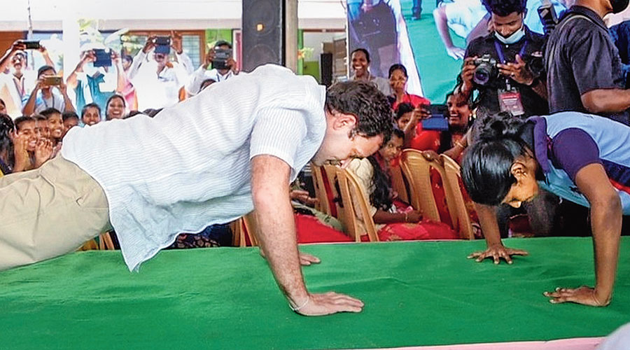 Rahul Gandhi accepts a push-up challenge from a student of St. Joseph's Matric Higher Secondary School at Mulagumoodu in Kanyakumari on Monday.