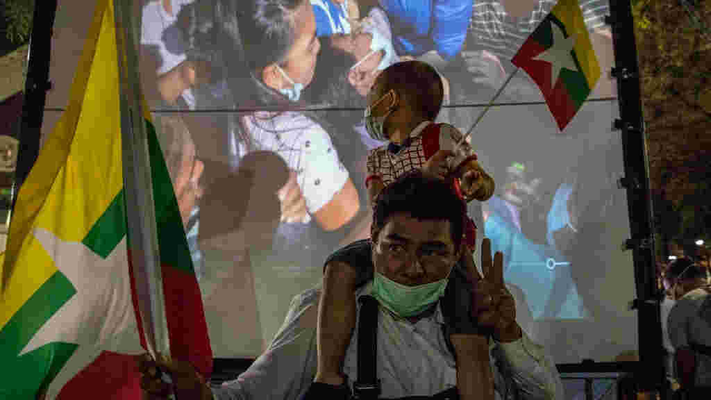 A Myanmar boy sits on his fathers shoulders as he watches a memorial video showing images for anti-coup protesters who were killed in Myanmar on March 04, 2021 in Bangkok, Thailand.