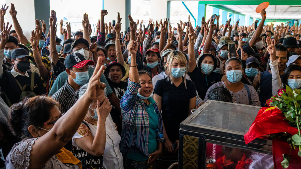 Relatives and supporters make three-fingered salutes while standing near the bodies of Ko Phoe Chit, 22, Arkar Moe, and Zwal Htet Soe, 26, during a funeral for protesters who were shot dead in clashes with military and police on March 05, 2021 at the Yay Way cemetery in Yangon, Myanmar.