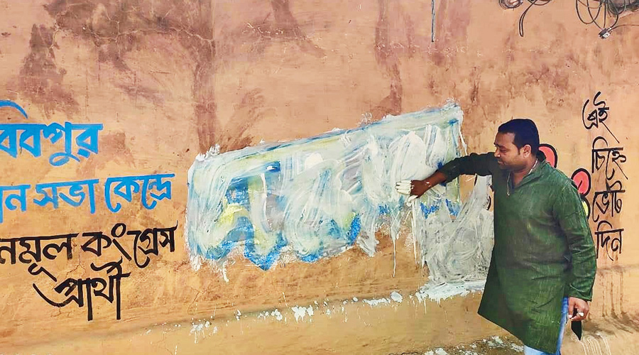 Trinamul candidate Sarala Murmu's graffiti being wiped out in Habibpur after she joined the BJP on Monday.