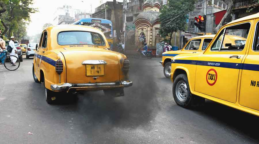 A taxi belching black fumes in the city.