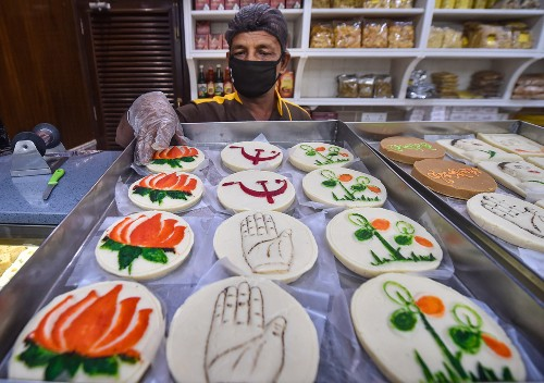 A vendor displays sweets with different political party symbols at his sweet shop, ahead of the State Assembly elections, in Calcutta