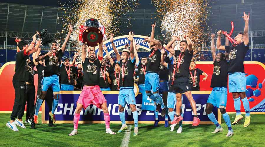 Mumbai City FC players and support staff celebrate with the trophy after winning  the ISL VII title at the Nehru Stadium in Fatorda on Saturday.