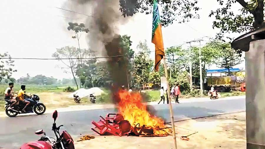 BJP supporters burn furniture and publicity materials in front of the party office in Karandighi of North Dinajpur on Friday.
