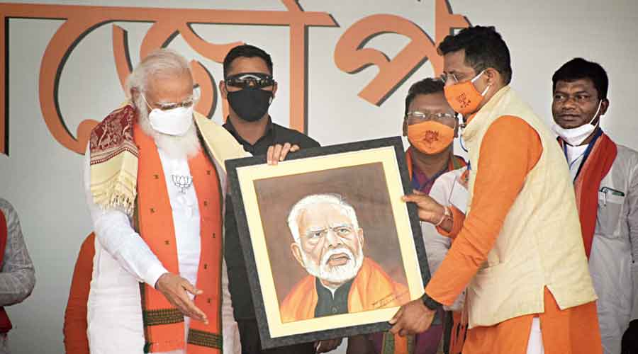 Prime Minister Narendra Modi gets a portrait of himself from party colleague Saumitra Khan, the MP from Bishnupur, in Bankura on Sunday