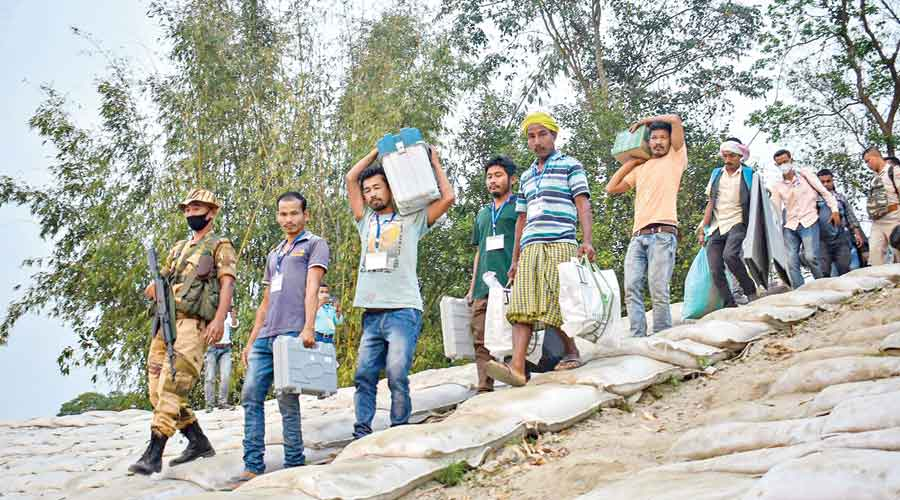 Polling officials leave for their assigned booths at Dhakuakhana, Assam
