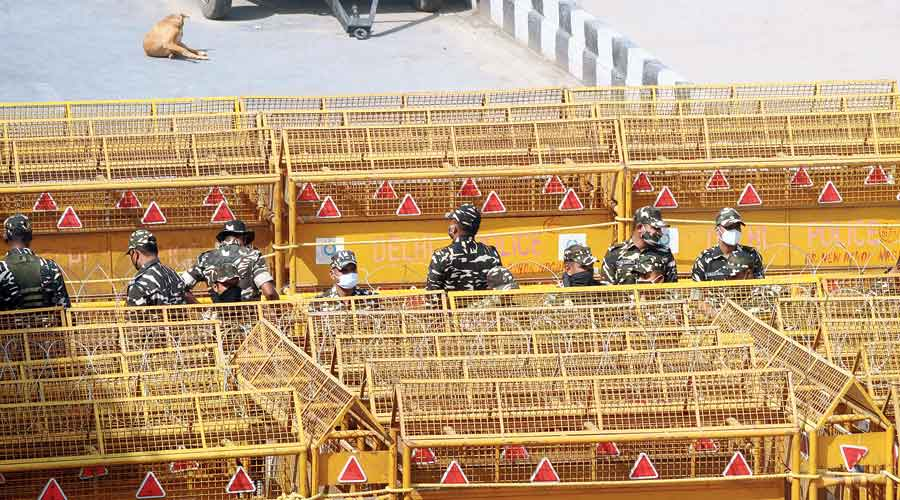 Policemen stand next to the barricades  at Delhi's Ghazipur border on Friday