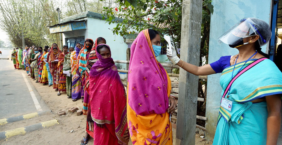 Voters undergo thermal scanning, as precaution against Covid-19, while waiting to cast votess at a polling station, during the first phase of West Bengal Assembly elections, at Sirshi in Jhargram, Saturday