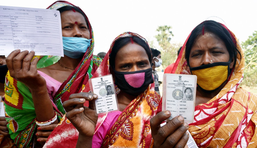Women show thier voter identity cards outside a polling station during the first phase of West Bengal Assembly elections, at Chandrapur in Lalgarh on Saturday.