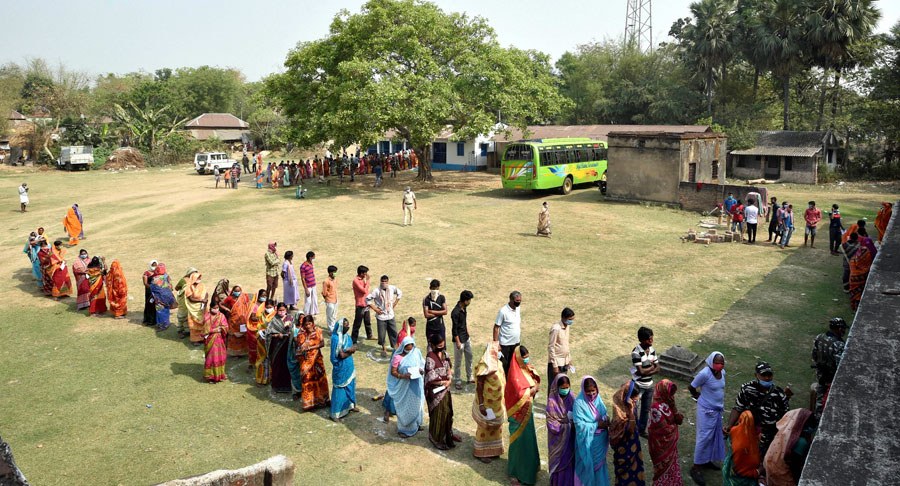 People wait in a long queue to cast their votes at a polling station during the first phase of West Bengal Assembly elections, at Chandrapur in Lalgarh on Saturday.