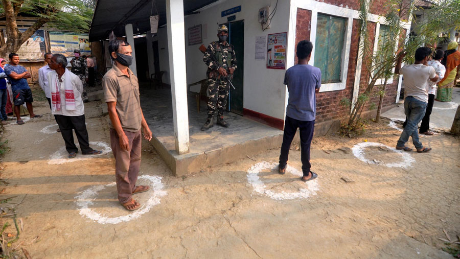 Voters queue up, maintaining social distancing, outside a polling station during the first phase of polling for Assam Assembly elections, at Amguri in Nagaon district on Saturday.