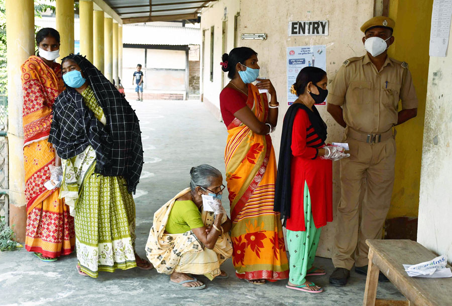 Voters queue up outside a polling station during the first phase of polling for Assam Assembly elections, at Rupohi in Nagaon district on Saturday.