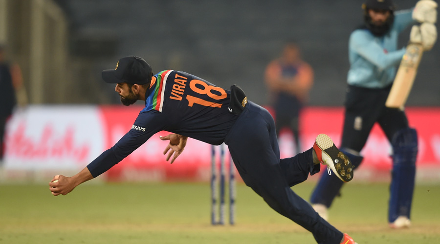 Indian captain Virat Kohli takes a catch to dismiss England batsman Adil Rashid during the 3rd one day international cricket match between India and England at Maharashtra Cricket Association Stadium in Pune on Sunday.