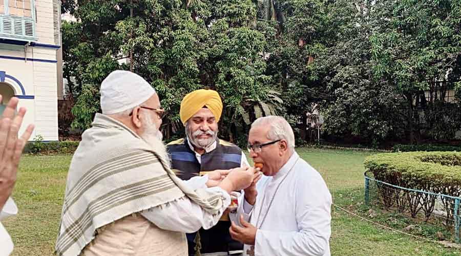 Maulana Qari Fazlur Rahman (left) and Archbishop of Calcutta Reverend Thomas D'Souza (right) offer sweets to each other as Satnam Singh Ahluwalia, the general secretary of Gurdwara Behala, looks on at the interfaith meet on Sunday