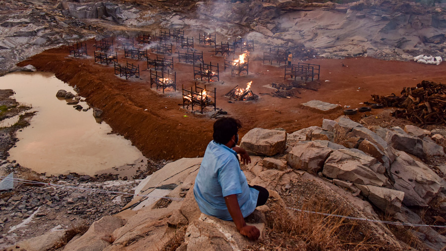 A man looks on during mass cremation of COVID-19 victims at a crematorium, on the outskirts of Bengaluru, Friday, April 30, 2021.