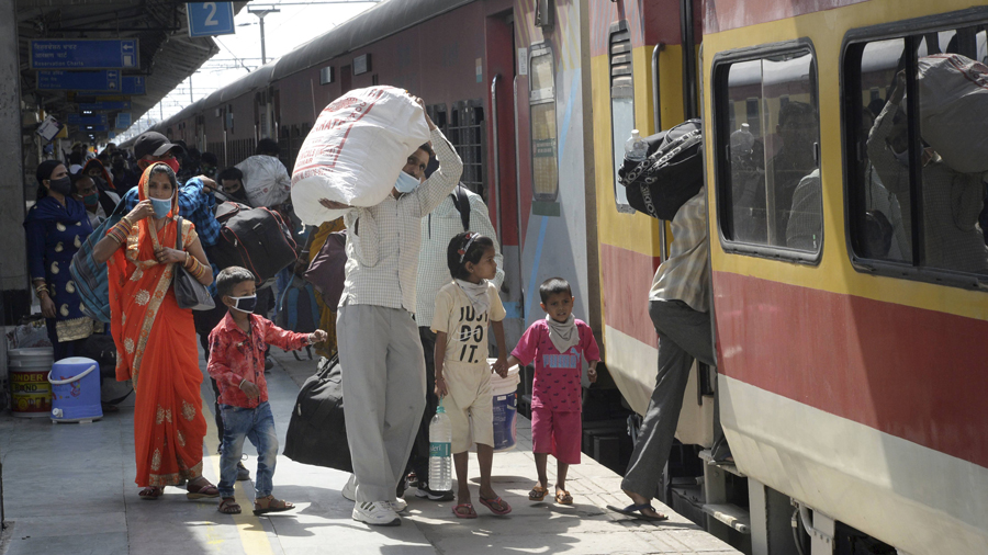 Migrants board a train towards their home states, amid spike in the numbers of positive coronavirus cases in the country, in Jalandhar, Friday, April 30, 2021.