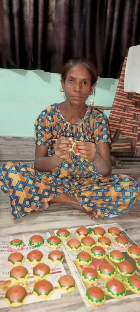 Ganga Bai paints diyas at her home in Jamshedpur on Tuesday.