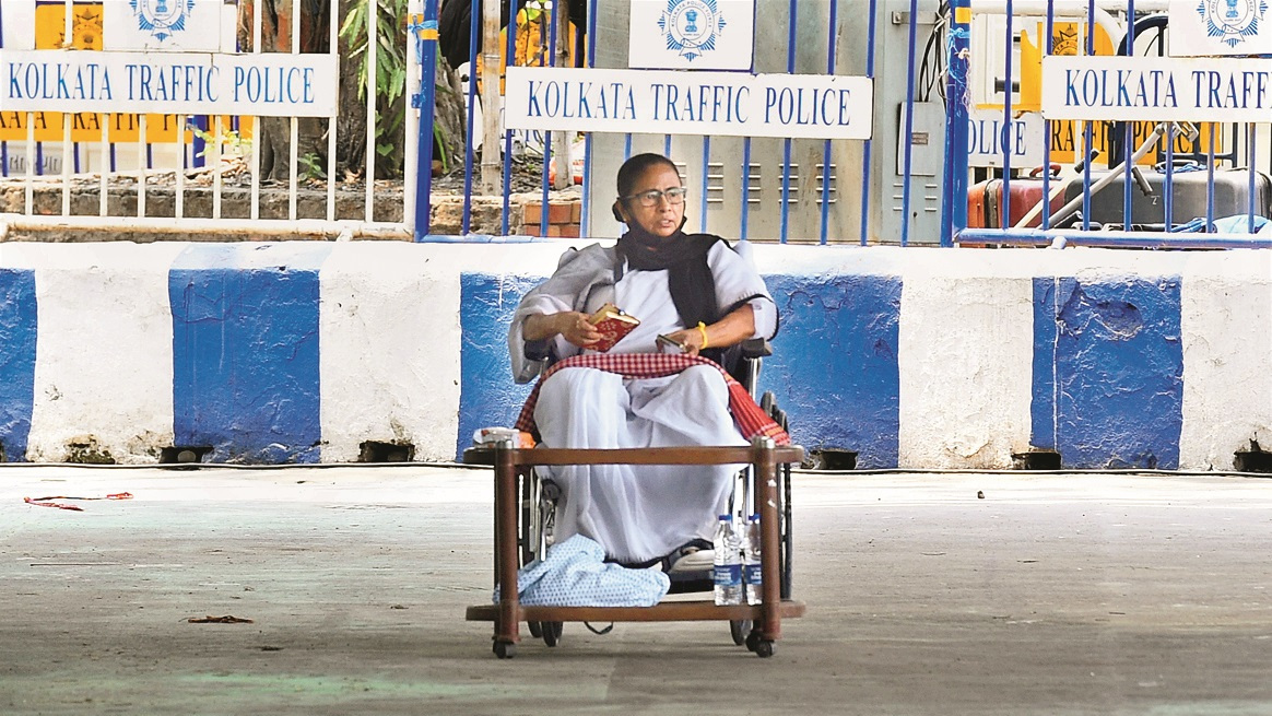 West Bengal Chief Minister Mamata Banerjee, sitting on a wheel-chair, stages a protest after EC imposed a 24-hour campaigning ban on the TMC leader, in front of the Gandhi Statue in Kolkata, Tuesday, April 13, 2021.