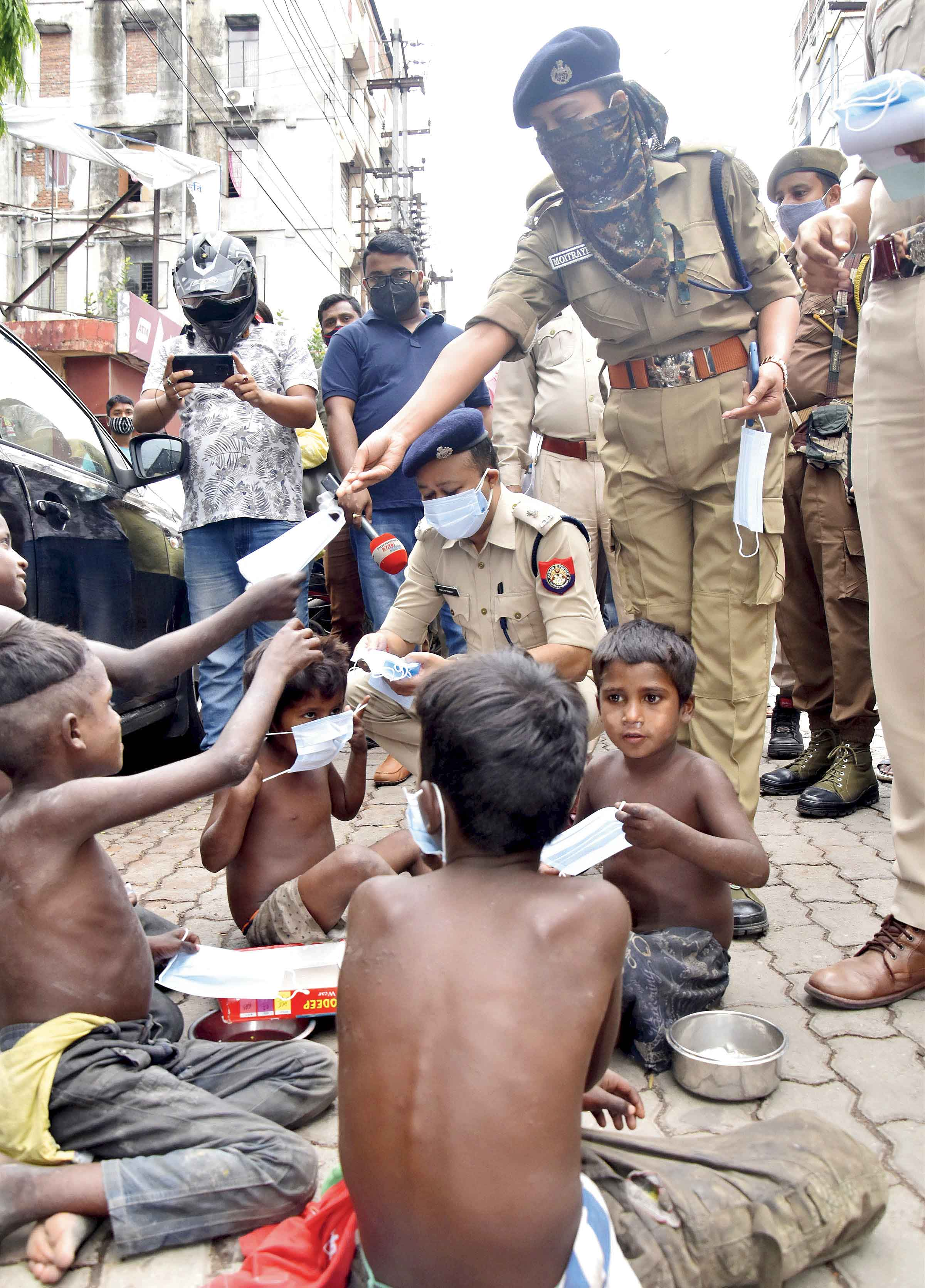 Police personnel distribute masks during an awareness campaign against the spread of the coronavirus in Guwahati on Tuesday