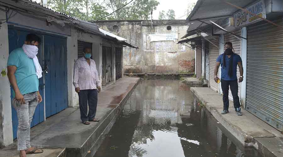 Traders of Darzee Patti at Municipal Market in Sindri stand in front their shops with a waterlogged road.