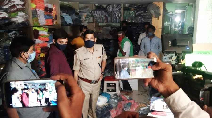 Police and district administration officials before sealing the shop on Sunday.