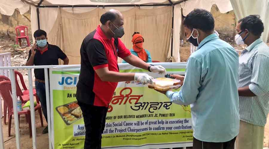 A JCI member gives a food packet at Sadar hospital premises to an attendant.