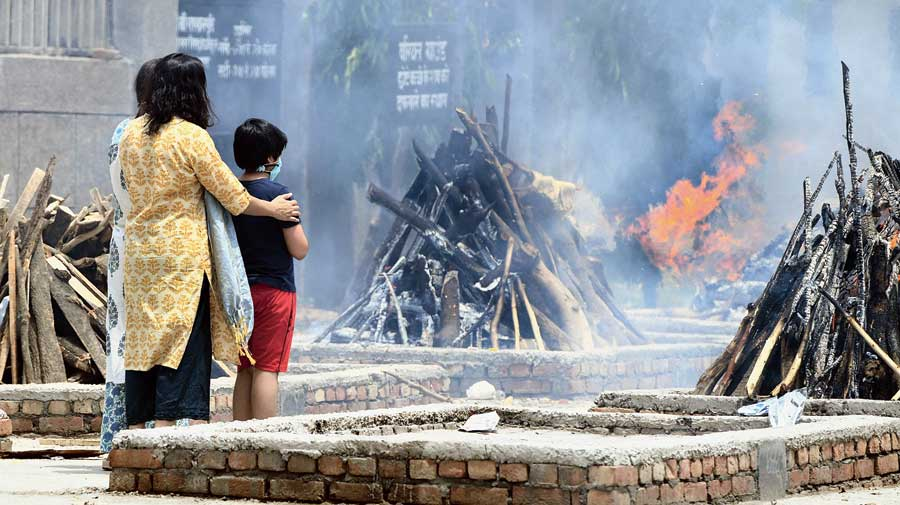 Family members of a Covid-19 victim watch the pyres burn at Sarai Kale Khan cremation ground in New Delhi.