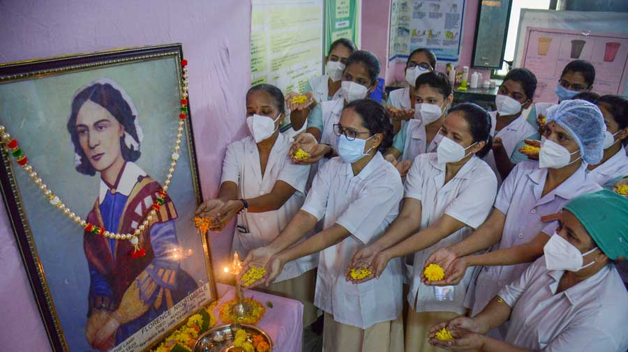 Nurses pay tribute to a portrait of Florence Nightingale on her birth anniversary in Thane.