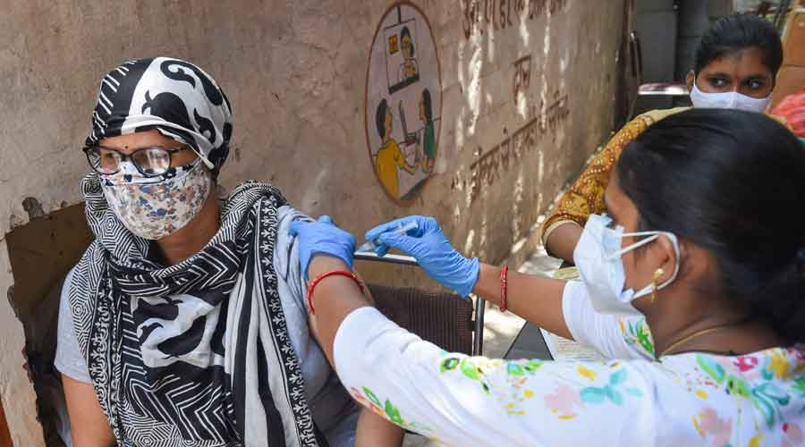 A medic administers COVID-19 vaccine dose to a beneficiary at a vaccination center, in Ghaziabad