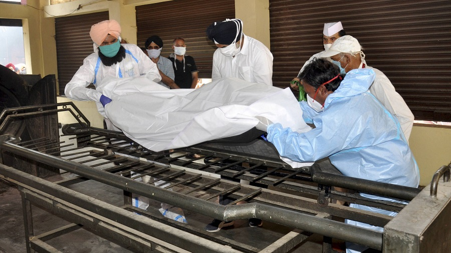 Health workers wearing personal protective equipment (PPE kit) carry the body of former minister of state for external affairs RL Bhatia at a crematorium in Amritsar on Saturday.