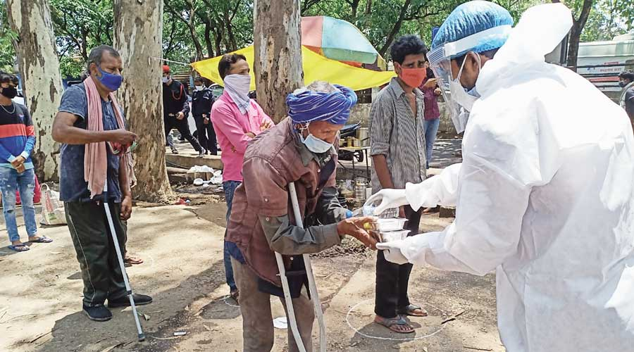 Members of the youth association distribute food items, ration and masks to villagers at Namkum block in Ranchi district on Saturday.