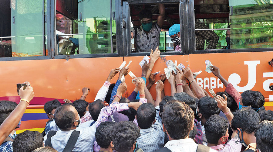 Passengers with money in their hands vie for the attention of the conductor to get tickets and board a bus headed to Midnapore from the Howrah station bus stand on Saturday, hours after the curbs were announced.