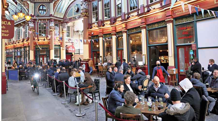 People enjoy having drinks outside a pub in London on April 16 when restrictions had eased