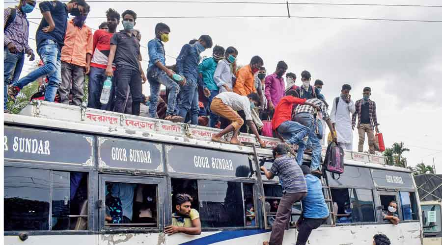 People clamber to the rooftop of a crowded bus in Nadia in a bid to reach home after the new curbs were announced on Saturday