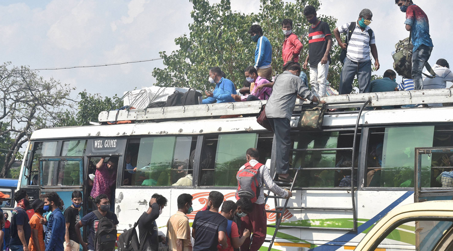 People, including migrant workers rush to board in a bus to leave the city, hours before the lockdown, after West Bengal Government announced complete lockdown till May 30 due to surge in coronavirus cases in Calcutta on Saturday.