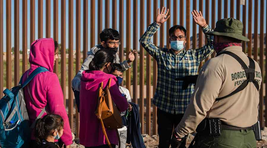 Families from India surrender to a US Border Patrol officer after crossing into the US in Yuma, Arizona