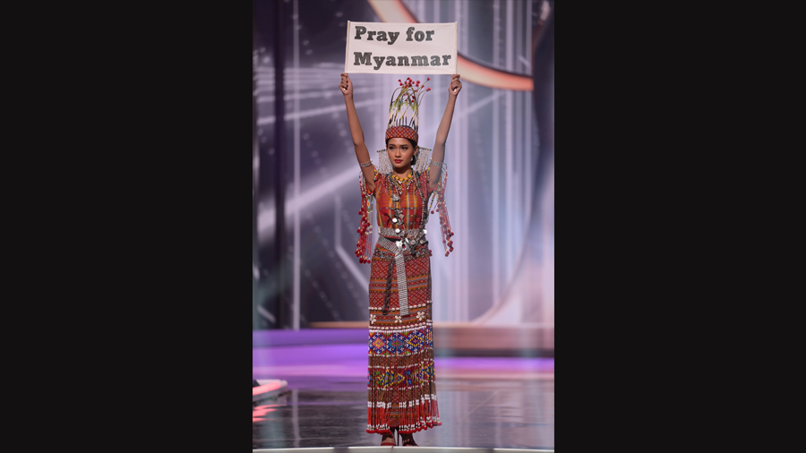 A photo provided by Benjamin Askinas shows Miss Universe Myanmar, Thuzar Wint Lwin, holding up a sign during the national costume show at the Miss Universe pageant in Hollywood, Fla., May 13, 2021.