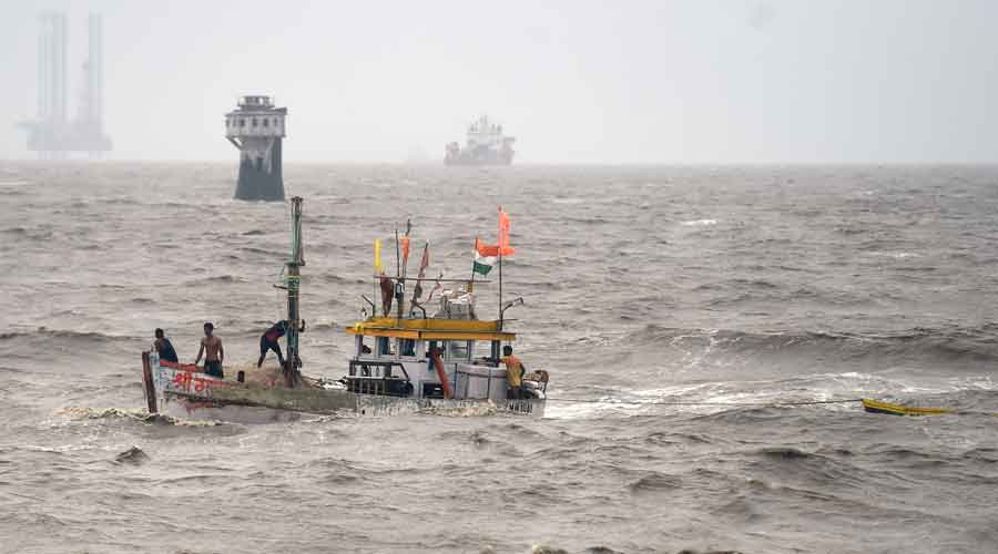 Fishermen on a fishing boat try to recover their smaller boat which had drifted away due to rough sea owing to Cyclone Tauktae, in Mumbai