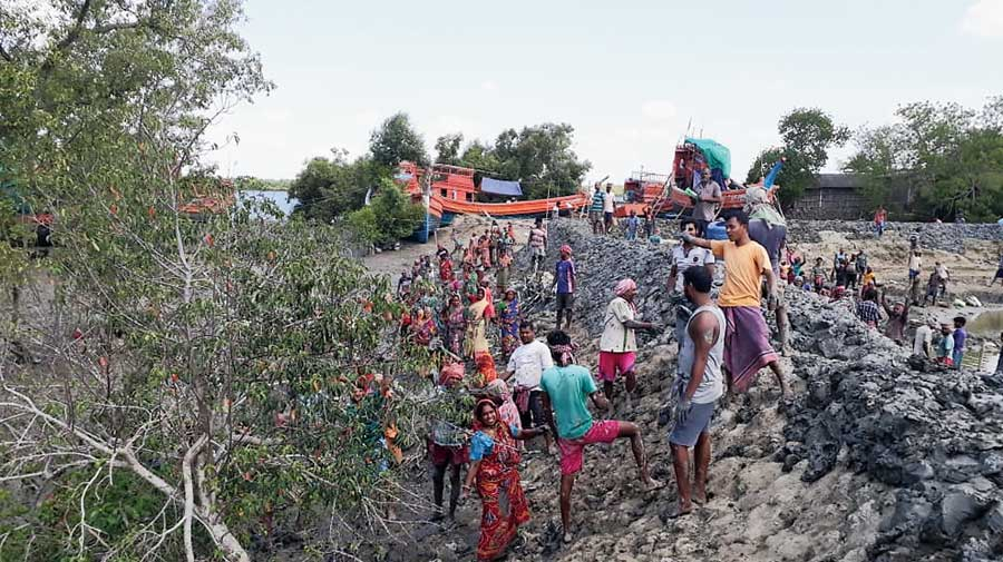 Villagers repair a river embankment in South 24-Parganas before the  landfall of Cyclone Yaas