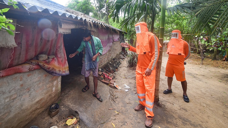 NDRF personnel alert people residing near coastal areas to evacuate ahead of Cyclone Yaas landfall, at Digha in East Midnapore district on Tuesday.
