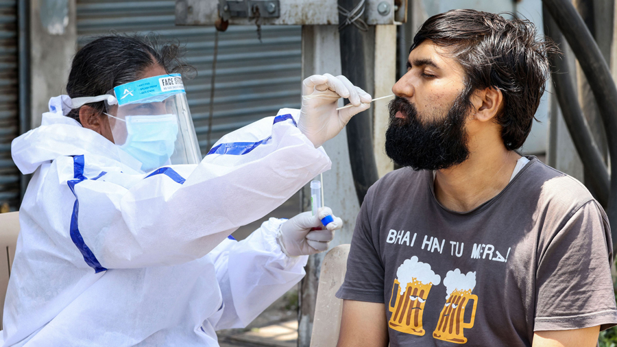 A health worker takes swab sample of a man for COVID-19 test at a medical camp organized by Coimbatore Corporation in Coimbatore, Wednesday, May 26, 2021.
