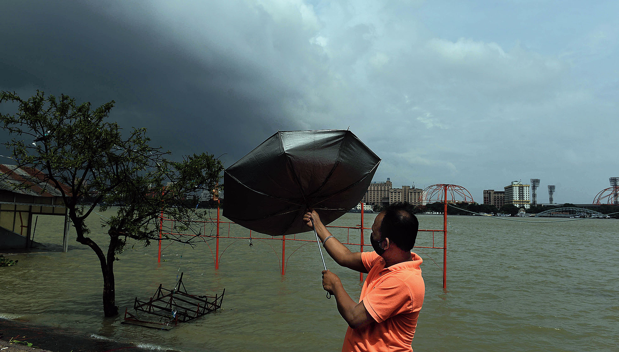 A man tries to adjust his umbrella amid strong winds at Ramakrishna Ghat in Howrah on Wednesday.