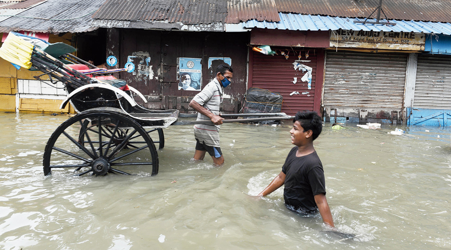 A rickshawpuller and a boy wade through a flooded  road in Kalighat on Wednesday.