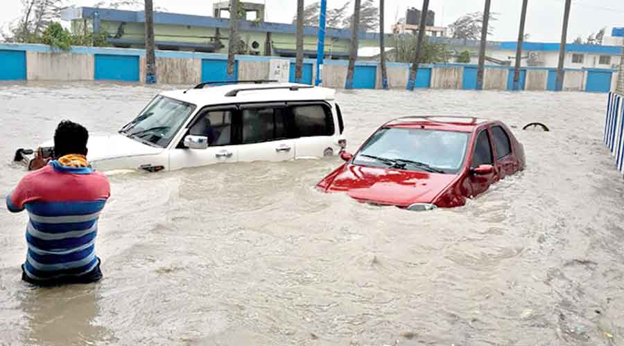 A man stands in waist-level water along with vehicles on a street in Digha