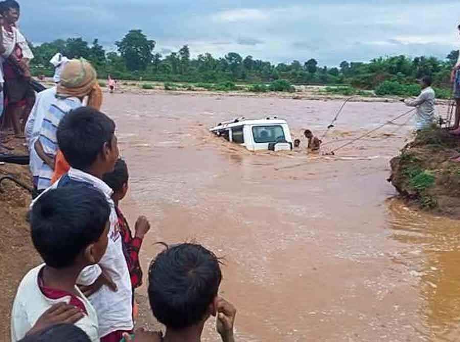 Villagers near Tupu Hesla of Latehar Sadar block rescue passengers stranded in a Bolero submerged in Dhardhari river.
