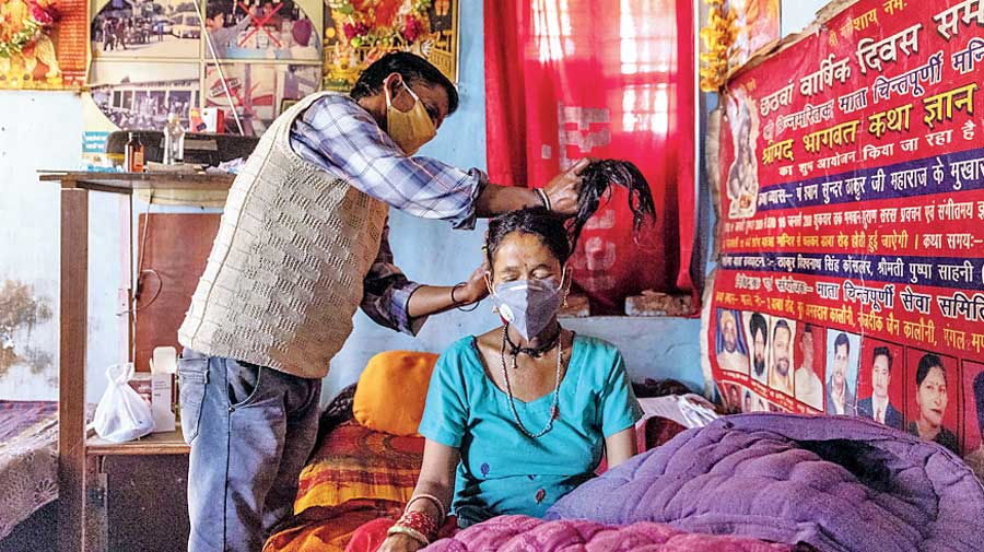 Pramila Devi's hair is tied up by her husband Suresh Kumar on May 23. A day earlier, she had tested Covid-positive