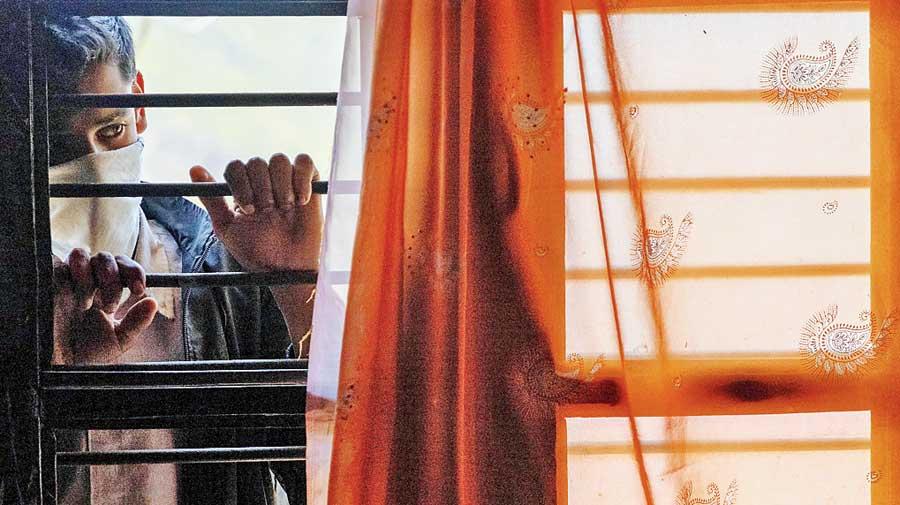 Their son Suraj Kumar, 16, watches his mother at  their home in Kaljikhal, Uttarakhand