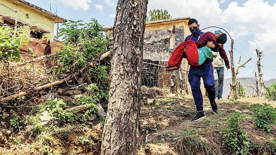 Rajesh carries Pramila to a local  government dispensary.